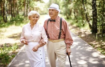 Elderly Couple Walking on a Path in the Woods