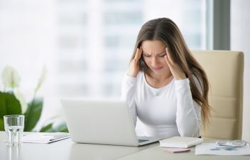 stressed woman with headache at her workplace